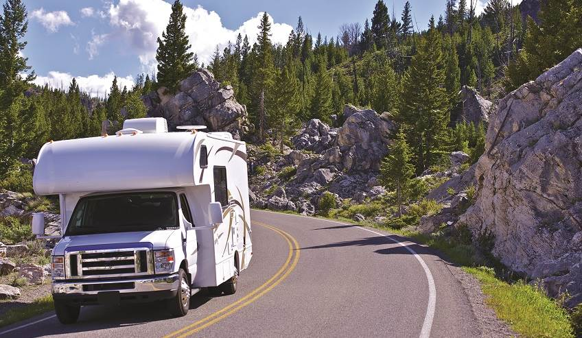 RV driving down the road in the mountains.