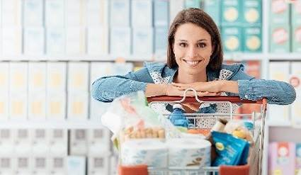 Woman in a grocery store with a cart full of packaged items.