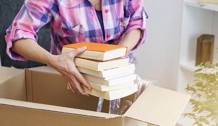 Woman packing books into a box.