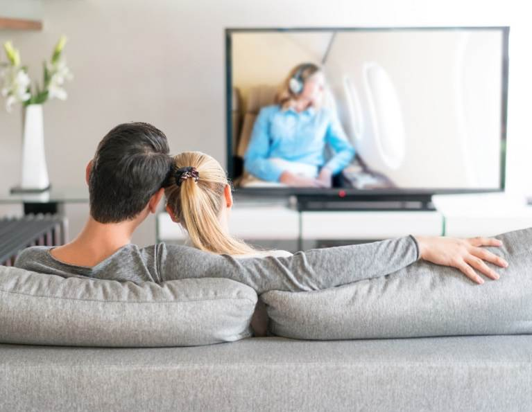 Couple watching TV representing display adhesives for the electronics manufacturing market from H.B. Fuller.