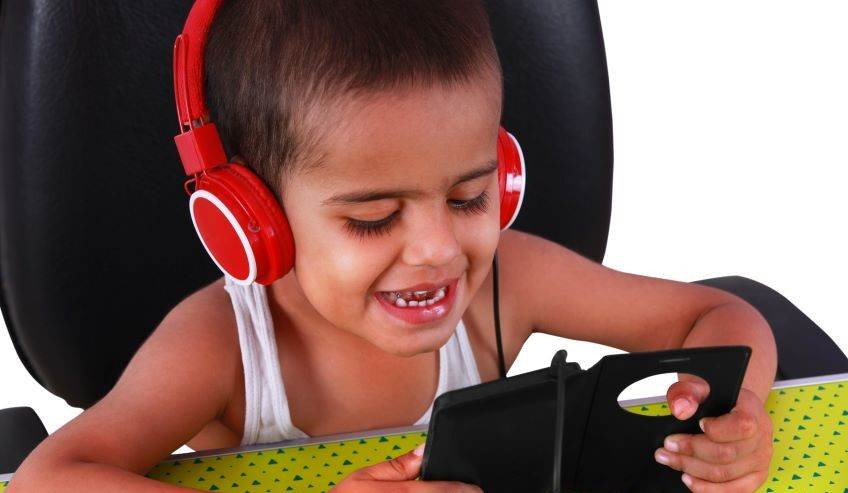 Boy with headphones looking at phone screen