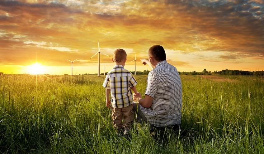 Man and boy sitting in a field looking at wind turbines