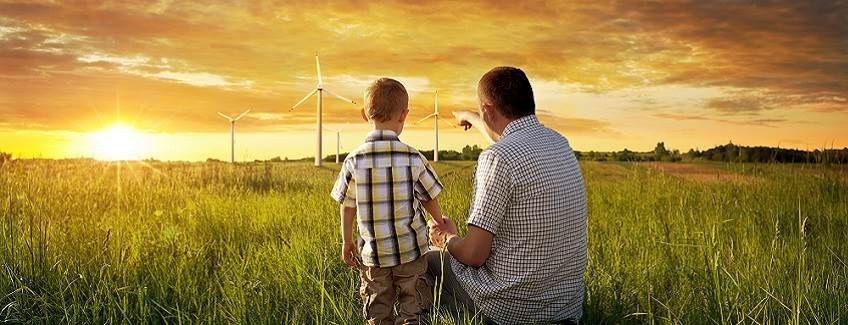 Father and son looking into the sunset with wind turbines.